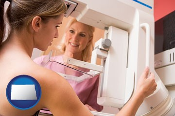 a nurse assisting a patient with a mammogram test - with North Dakota icon